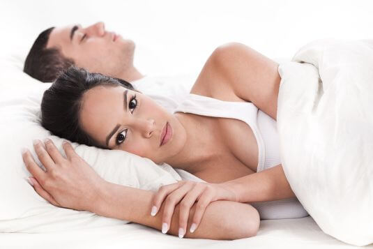 Couple in bed, men sleeping and woman lying sleepless