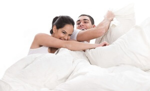 Playful young beautiful couple with pillows in bed cover white sheet